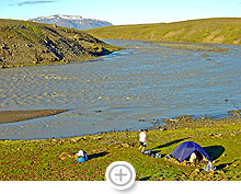 Building a stone wall to keep the tent safe, river Jökulfall, Iceland Highlands